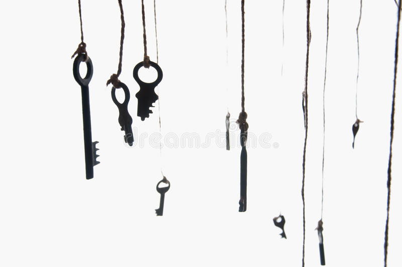 Many rustic keys hanging on string. Selective focus. Isolated stock photography