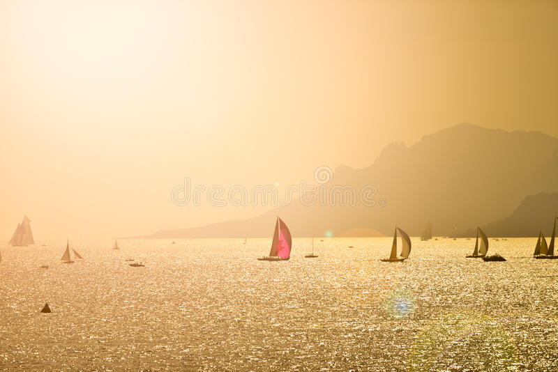 Many Sailing Boats At Sunset With Montain stock photo