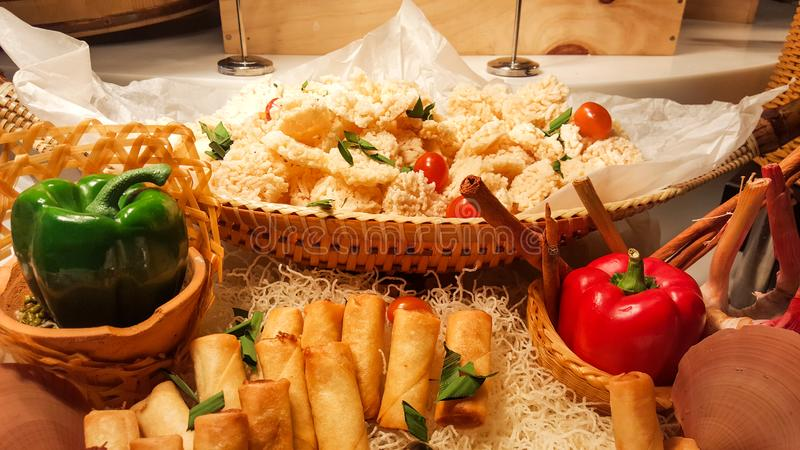 Many of salty snack that including crispy rice, fried spring rolls, tomato and pretzels served as party food in the wooden bar stock photography