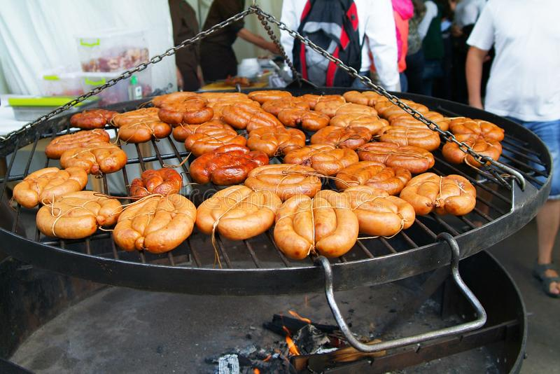 Many sausages on the grill stock images