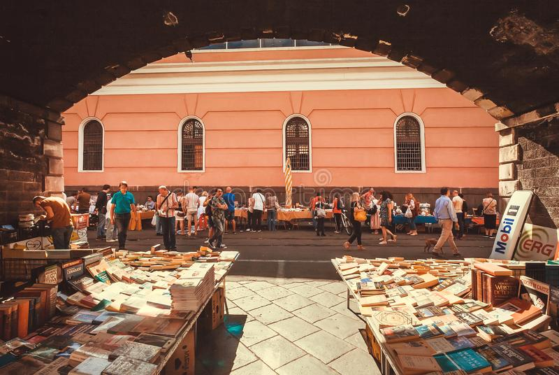 Many second hand books for sale and customers walking around weekend antique market of historical city stock photography