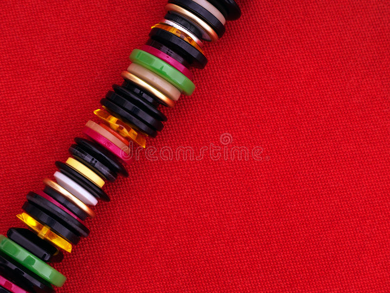 Many sewing buttons on red fabric - sewing, dressmaking background royalty free stock image