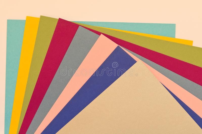 Many sheets of colored paper on a light background stock images