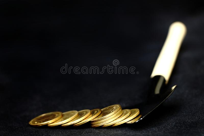 Many shiny golden coins pile on black shovel on black background, concept digging golden coins for royalty free stock photography