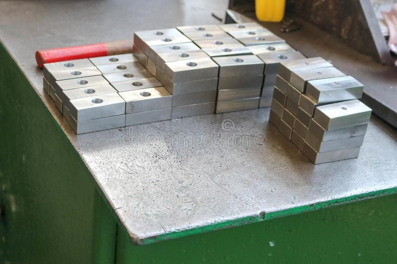 Many shiny metal, square ingots, blanks with drilled holes, metalwork tools and industrial grips on the robotic green table in the royalty free stock photography