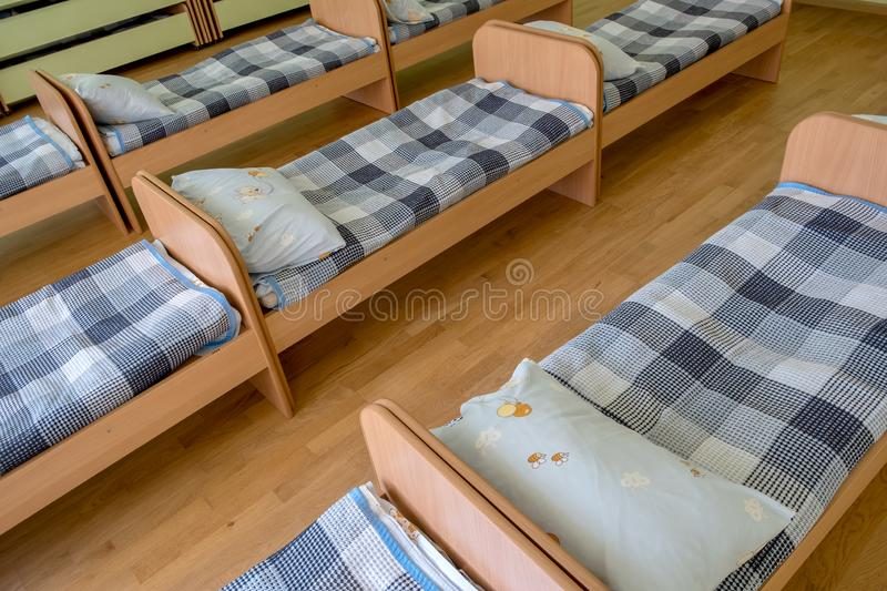 Many small beds in daycare preeschool empty bedroom.  stock photos