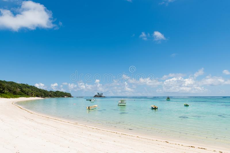 Many small boats near indian ocean coastline. Seychelles beach with transparent water and vessels. Many small boats near indian ocean coastline stock photography