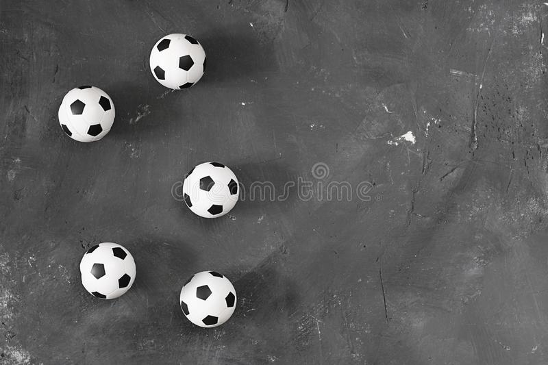 Many small football balls on black textured chalkboard background with copy space for text and design. Top view. Sport. Many small football balls on black stock photography