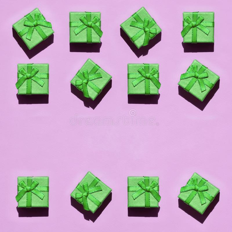 Many small green gift boxes on texture background of fashion trendy pastel pink color paper stock photo