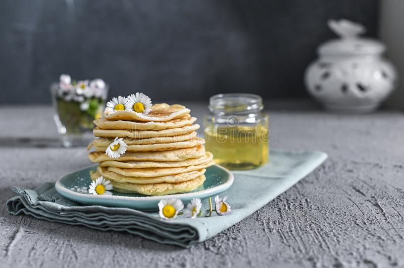 Many small pancakes with honey or syrup. Delicious traditional breakfast. Spring flowers as food styling in photography. Gray. Stone background and dessert is stock image