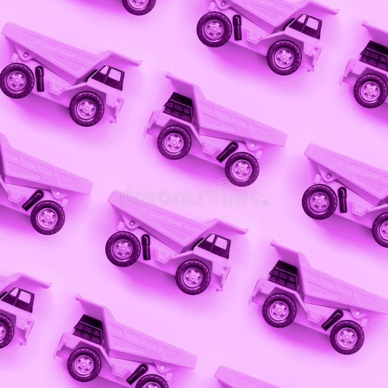 Many small purple toy trucks on texture background of fashion pastel purple color paper stock photography