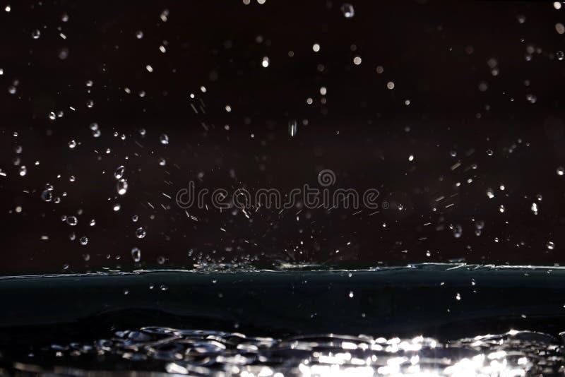 Many small raindrops glisten in the sun. Rain falls on the ground stock photos