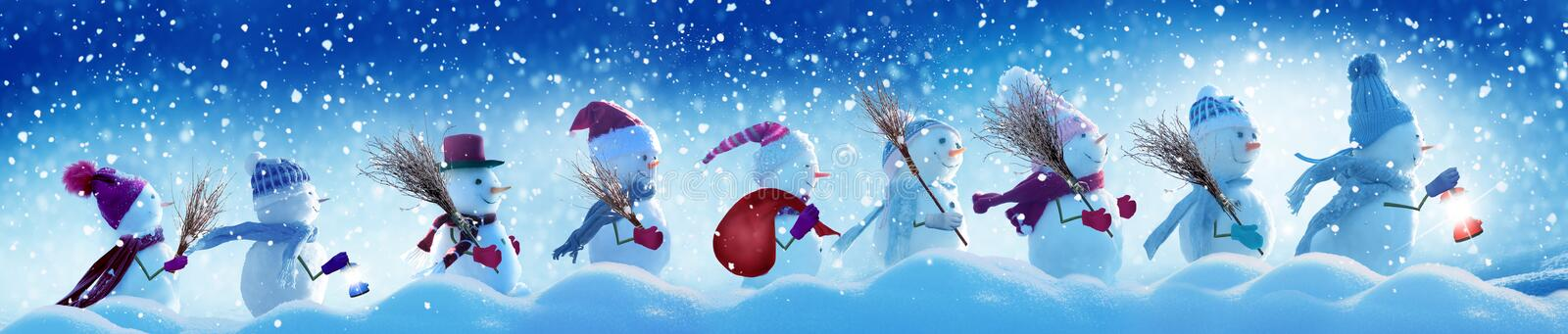 Many snowmen standing in winter Christmas landscape. stock photos