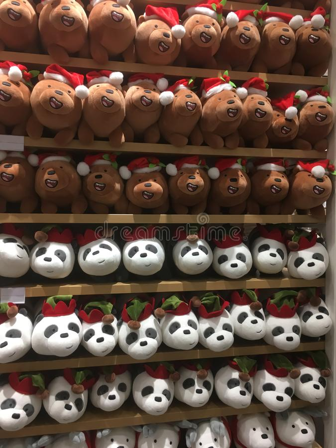 Many soft toys - pandas and polar bears on shop shelvesMany soft toys - pandas and bears wearing Santa`s hat on shop shelves royalty free stock photo