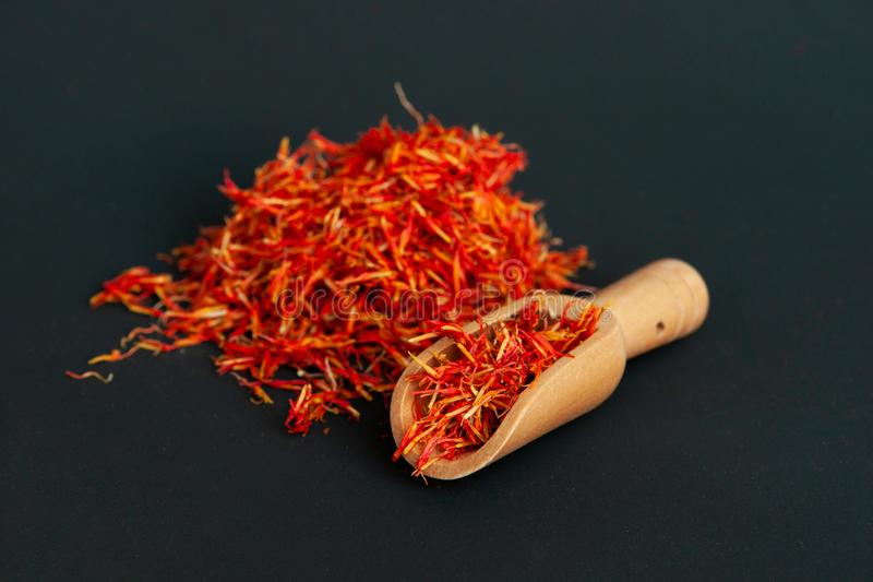 Many spicy saffron spice in the whole background with a wooden spice spatula.  royalty free stock photos