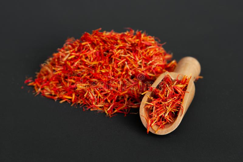 Many spicy saffron spice in the whole background with a wooden spice spatula.  royalty free stock photography