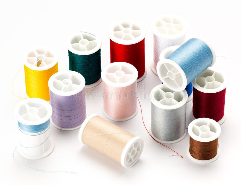 Many spools of different colored thread on a white table top royalty free stock photo