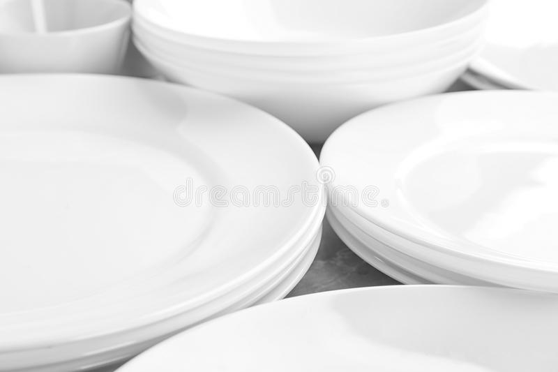 Many stacked white plates on table stock photos