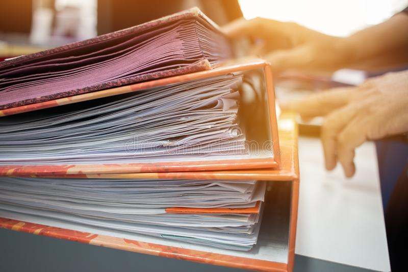 Many Stacks of document folders in office for Annual Report file. S on Abstract blurred photo of businessman hands working with laptop computer. business busy royalty free stock image