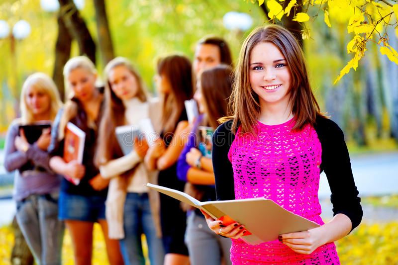 Many students in the autumn park. Many young girls in the autumn park with books stock photos