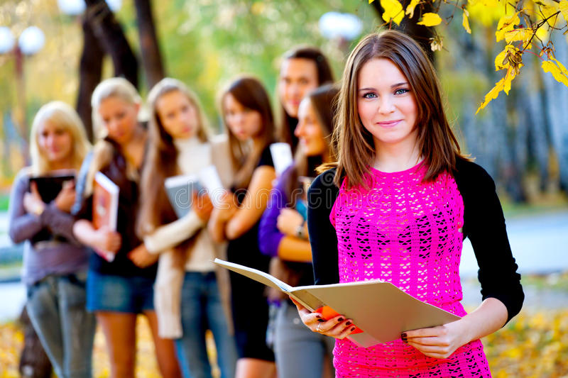 Many students in the autumn park. Many young girls in the autumn park with books royalty free stock photography