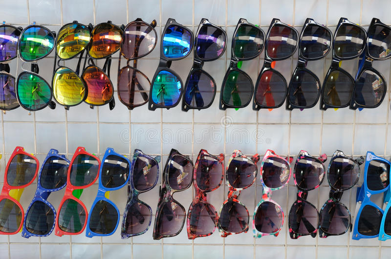 Many style of sun shades glasses on display. A photo taken on many sun shade glasses hanging on display. They comes in different design, colors and style stock photos