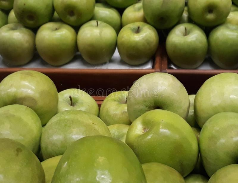 Many succulent green apples. Green apples in a market gondola with mirror many succulent royalty free stock photos
