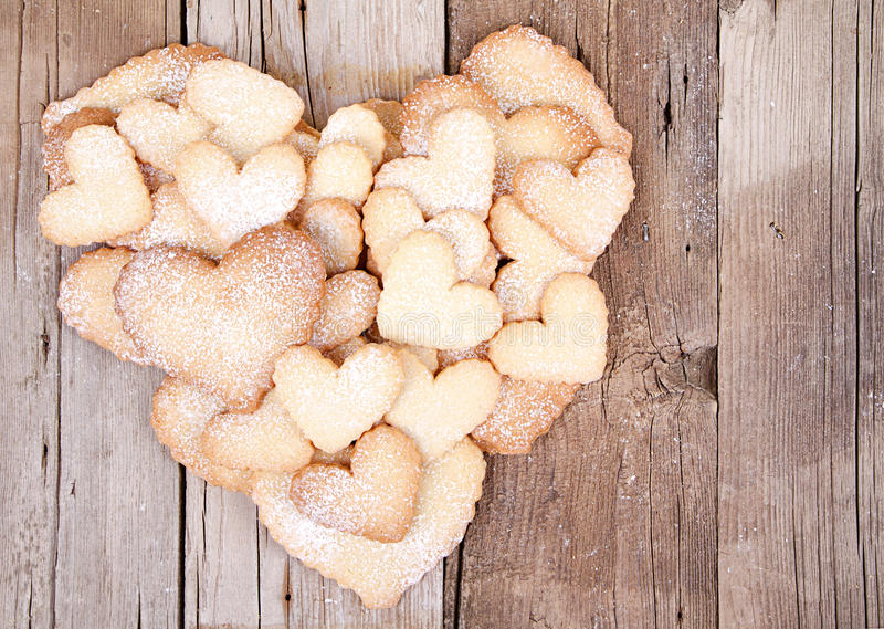 Many sugar cookies stacked in heart shape. Heart shaped sugar cookies stacked in the shape of a heart on wooden background royalty free stock photo