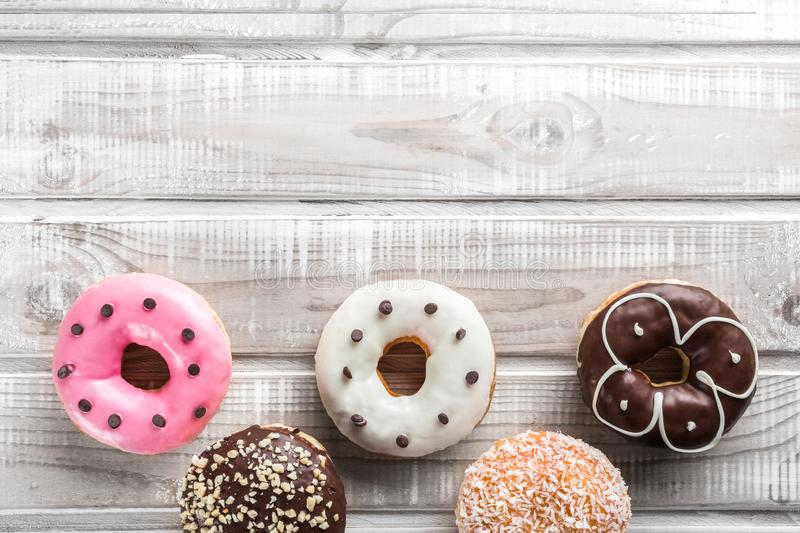 Many sweet donuts on an old wooden table, placed at the bottom, top view stock photo
