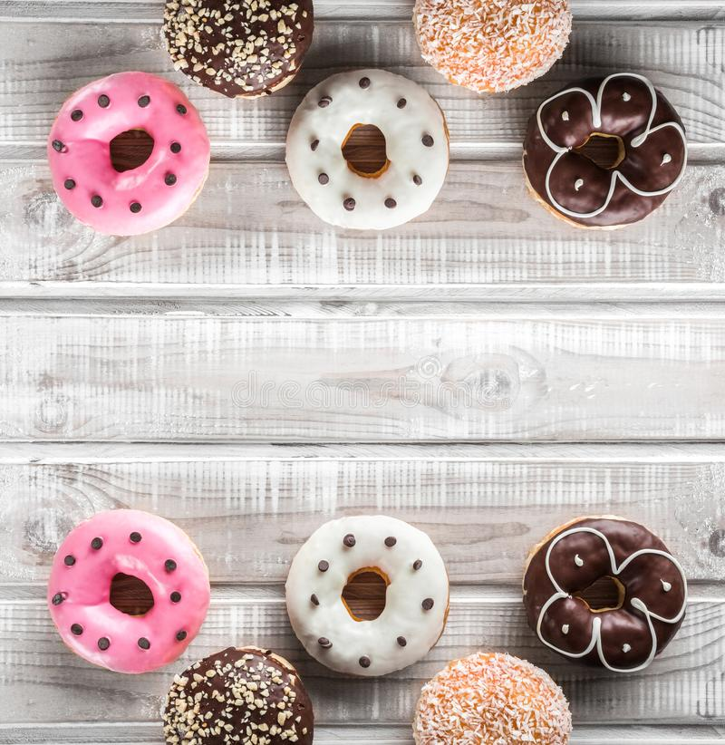 Many sweet donuts on an old wooden table, top view, space for text. Double mirror effect.  stock image