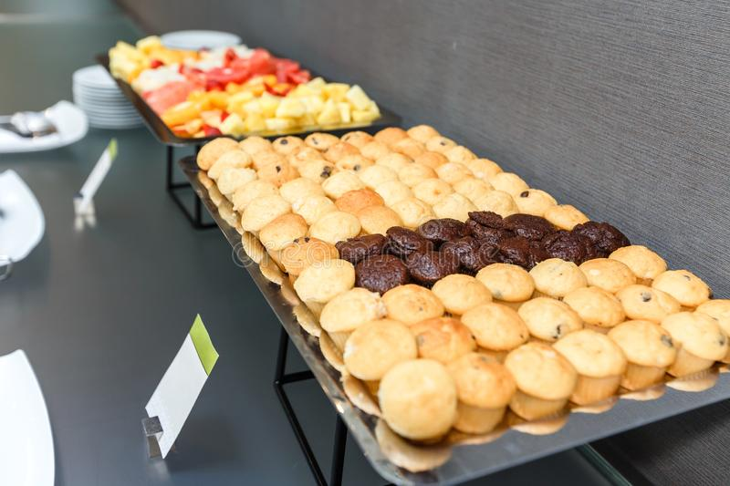 Many Sweet muffins and sliced fruits on table on a coffee break in the office. Many Sweet muffins and sliced fruits on a table on a coffee break in the office royalty free stock photography