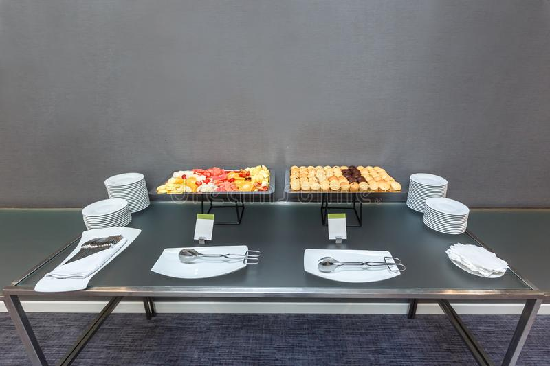 Many Sweet muffins and sliced fruits on table on a coffee break in the office. Many Sweet muffins and sliced fruits on a served table on a coffee break in the stock photography