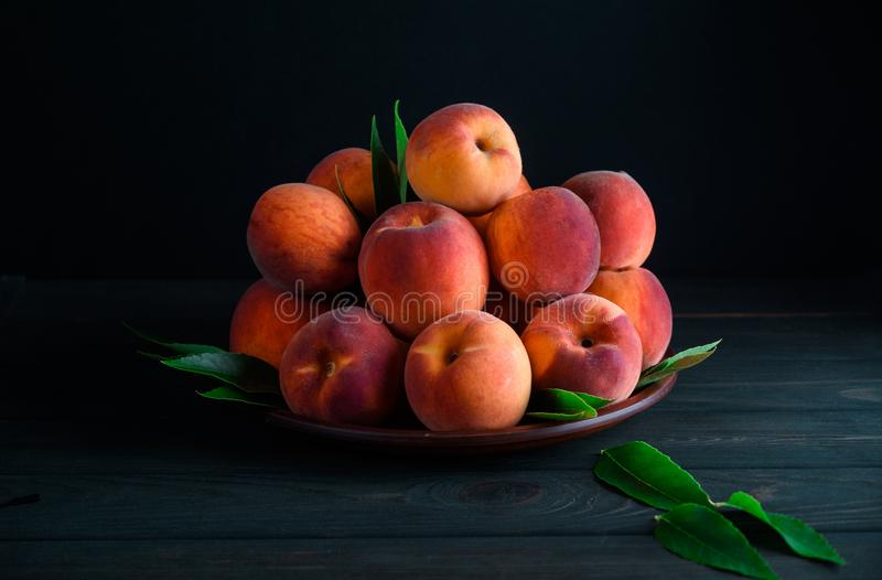 Many sweet peaches in a plate stock image