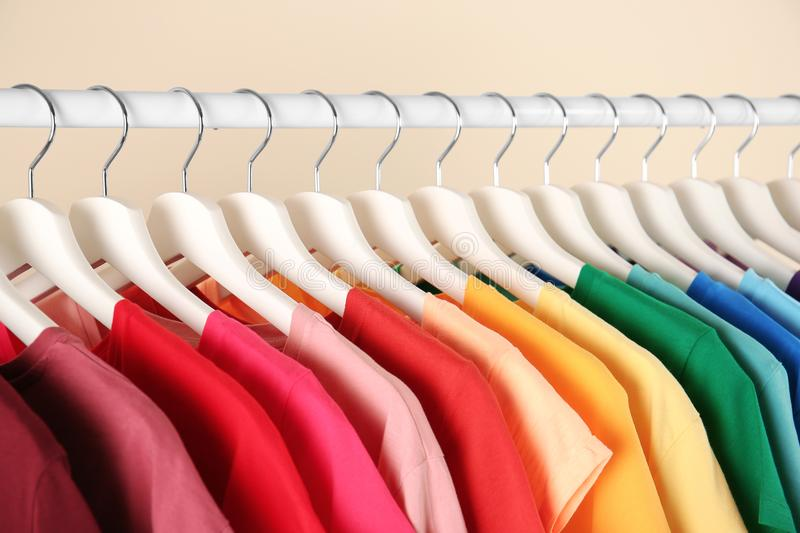 Many t-shirts hanging in order of rainbow colors. Closeup stock images