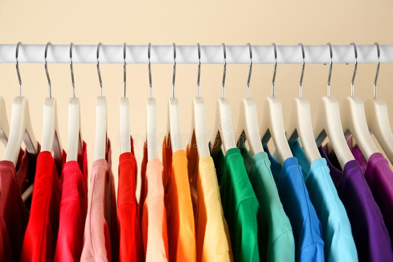 Many t-shirts hanging in order of rainbow colors. Closeup royalty free stock photos