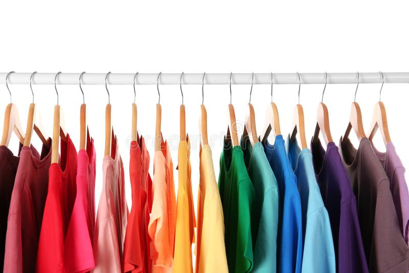 Many t-shirts hanging in order of rainbow colors. Closeup royalty free stock image