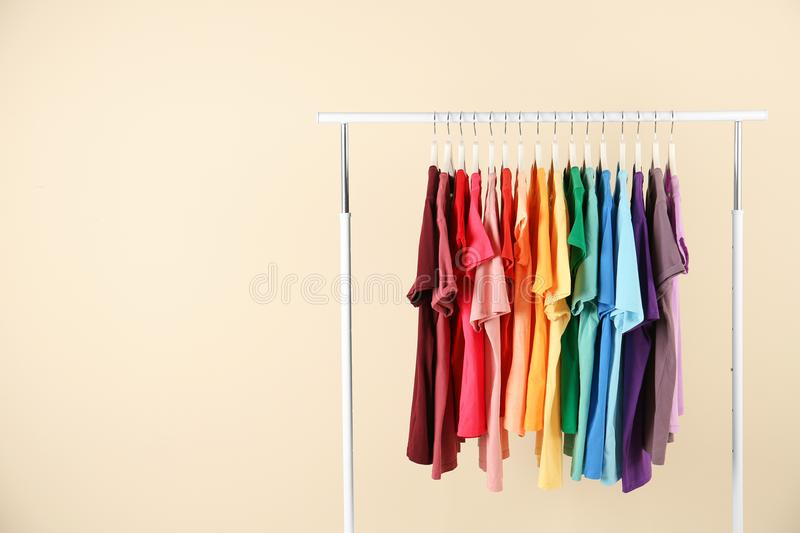 Many t-shirts hanging in order of rainbow colors. On light background royalty free stock images