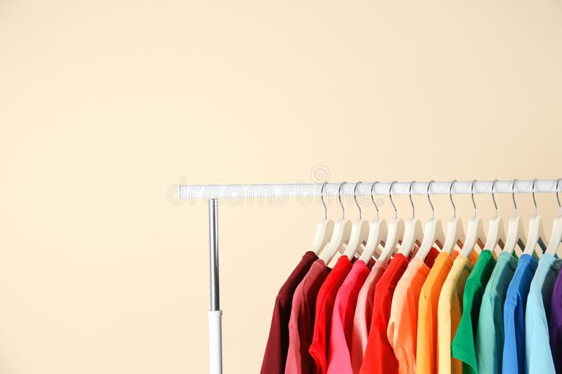 Many t-shirts hanging in order of rainbow colors. On light background royalty free stock photography