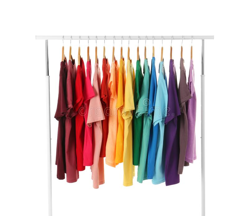 Many t-shirts hanging in order of rainbow colors. On white background stock photography