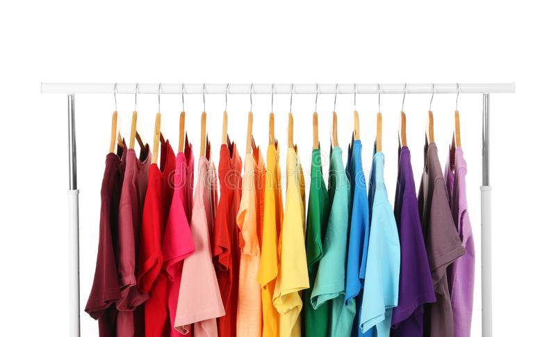 Many t-shirts hanging in order of rainbow colors. On white background royalty free stock photos