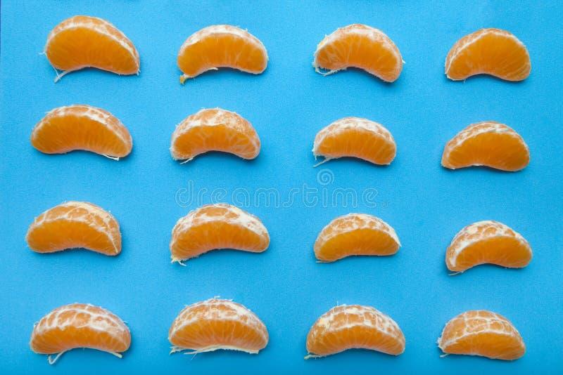 Many tangerine slices on blue background stock photos