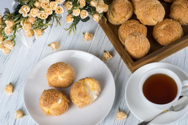 Many tasty cakes of Shue from custard paste with cream stuffing. Lie on a round plate on a white wooden table. One cake is cut and cream is visible. A tray with stock photos