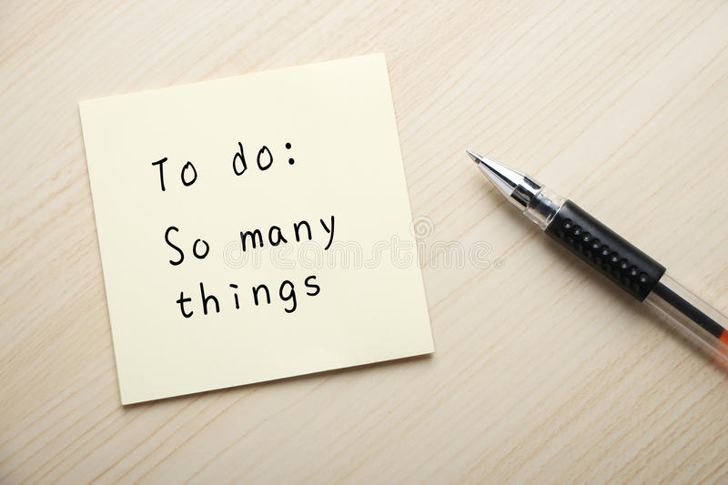 So many things to do. A yellow sticky note is written something on the desk with a ball pen aside stock photo