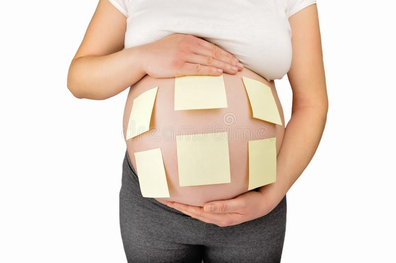 So many things to do before you arrive. Shot of an unidentifiable pregnant woman with adhesive notes stuck to her belly stock photography