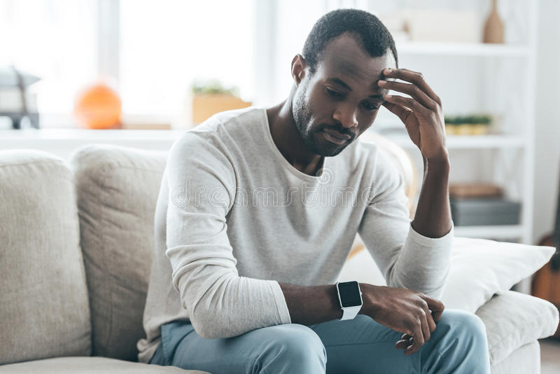 Many things to think about. Handsome young African man touching head with hand and looking uncertain while sitting on the sofa at home stock images