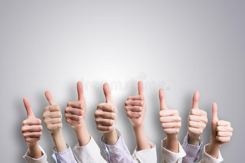 Many thumbs up on grey background royalty free stock photo