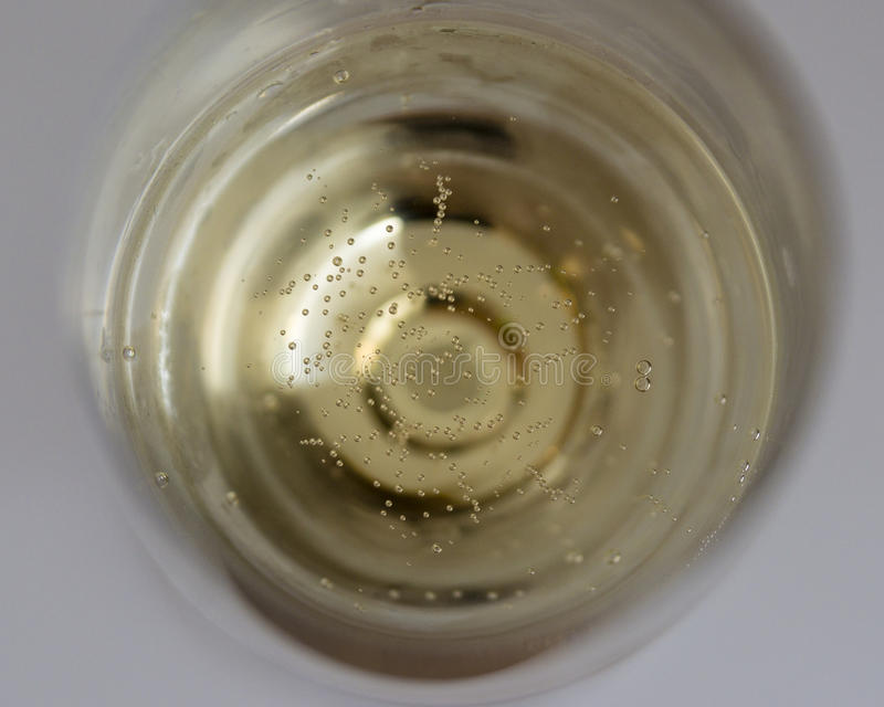 Many tiny bubbles in a champagne glass. Many tiny golden bubbles in a champagne glass from above royalty free stock images