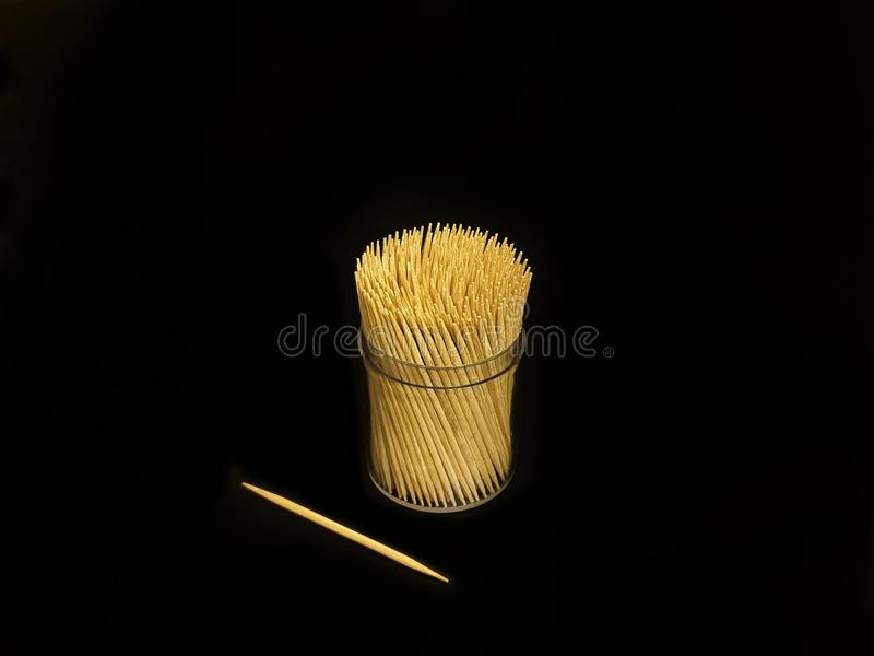Many toothpicks are in a clear cylindrical plastic box stock photo