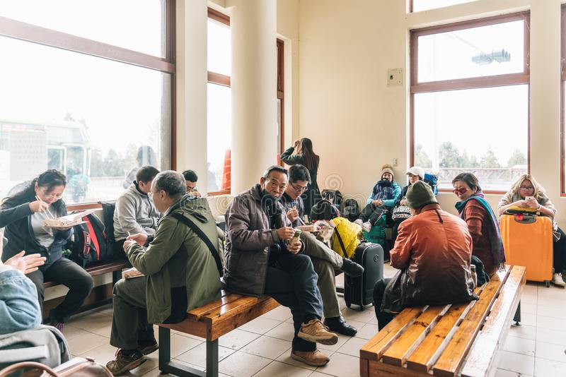 Many tourist are wearing coats eating and wait a bus for going to Taipei inside bus station in winter in Alishan, Taiwan royalty free stock photos
