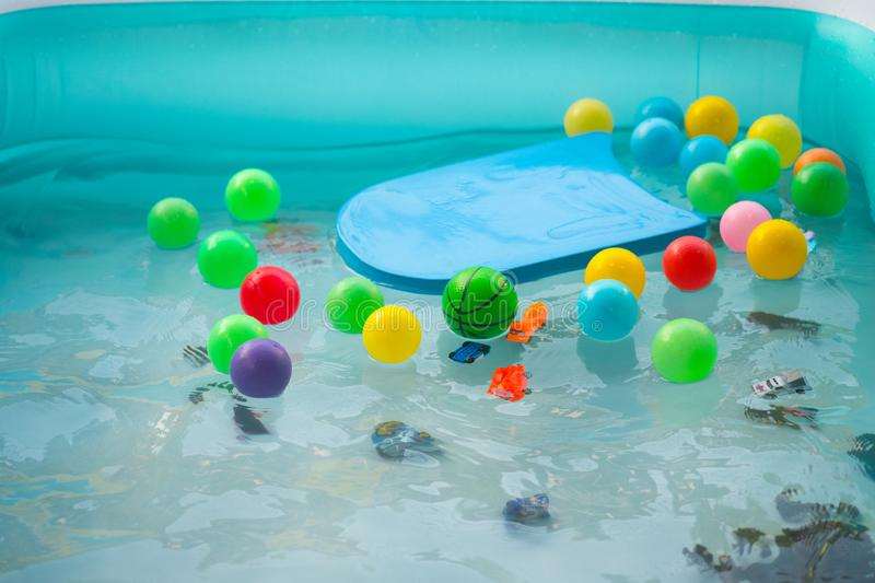 Many toy floating in outdoor swimming inflated pool. Concept for summer vacations, relaxation and fun in the sunshine stock photo